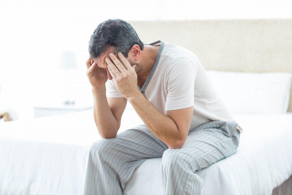 Homme triste assis au bord de son lit